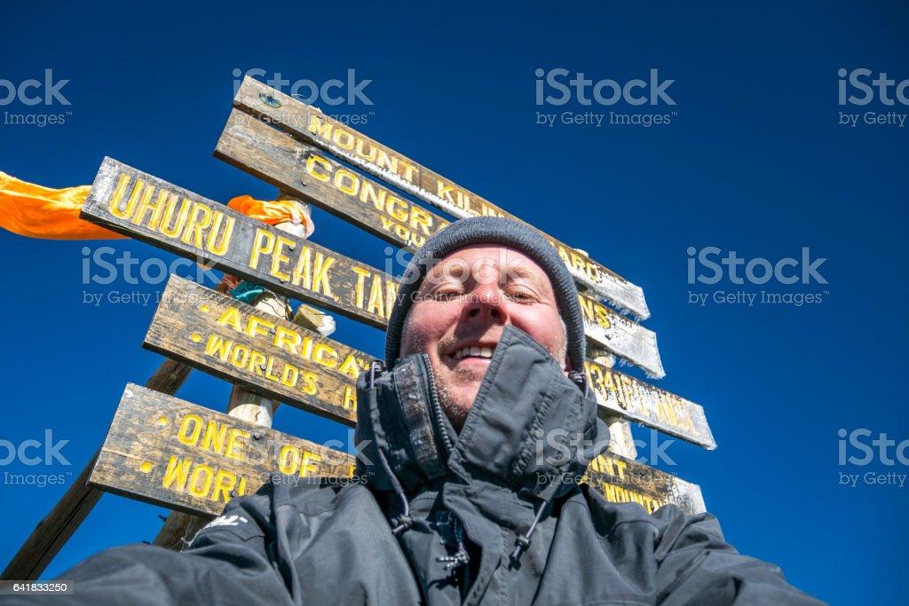 Man at Uhuru Peak, Mount Kilimanjaro stock photo