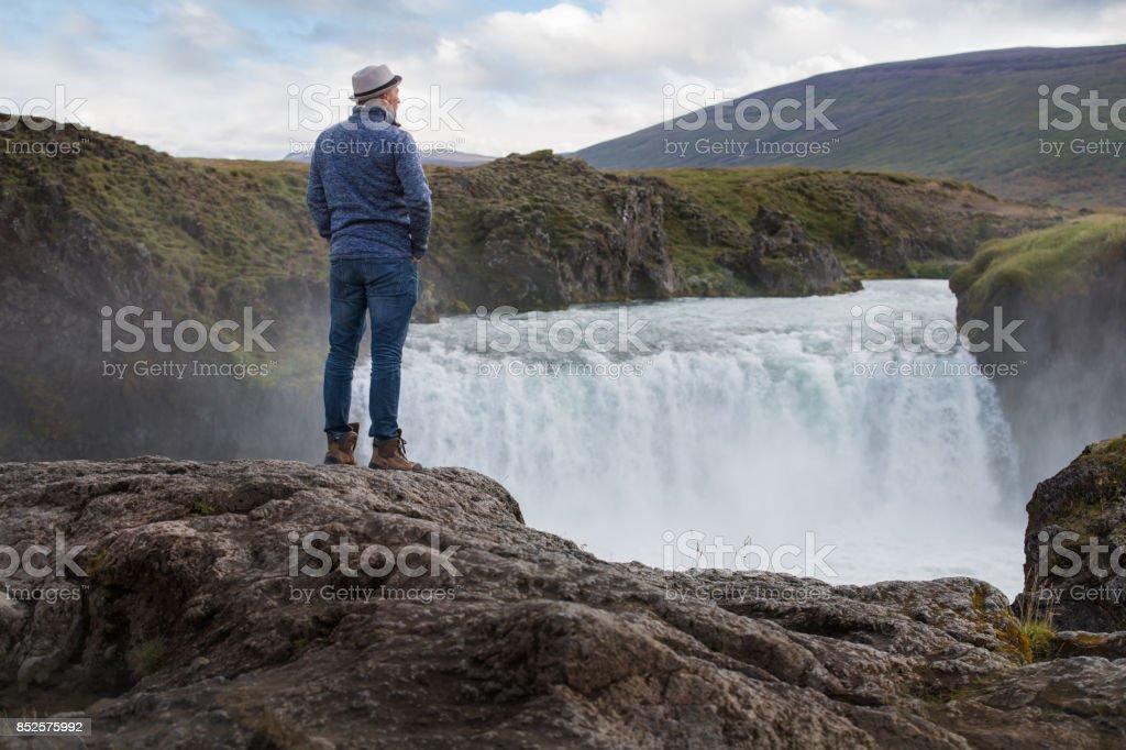 Homem em Cachoeira na Islândia - foto de acervo