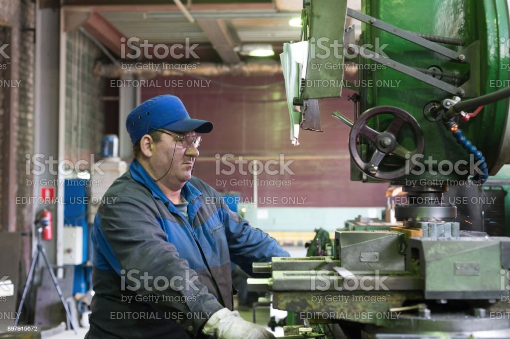 A man at work on a vertical milling machine. Machining of a metal part on a metal-cutting machine stock photo