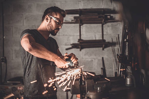 Man at work. Confident young man grinding with sparks in repair shop grinding stock pictures, royalty-free photos & images