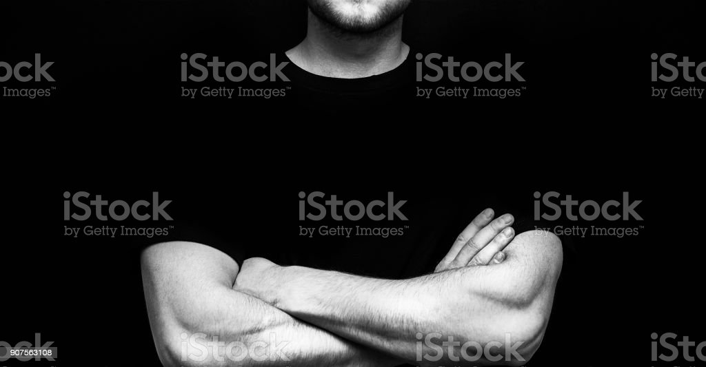 man athlete, bodybuilder in black t-shirt with arms crossed on the body on the black background,t shirt mock up stock photo