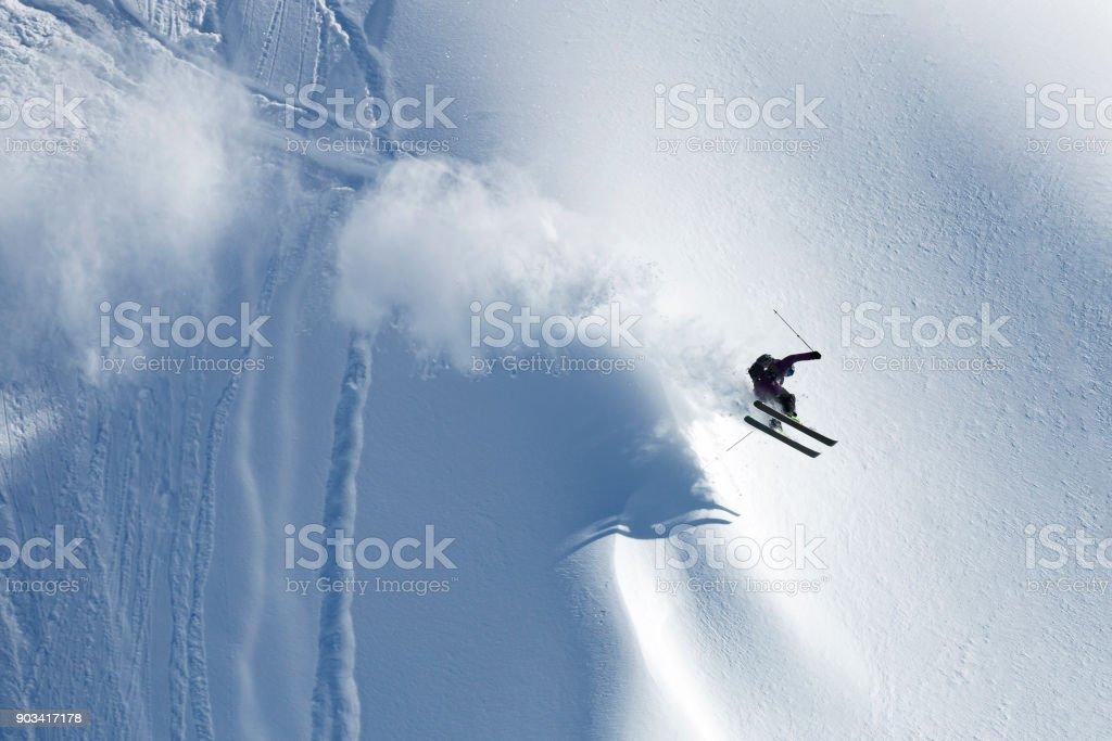 Man athlete doing skiing stunts on sunny alpine slopes stock photo
