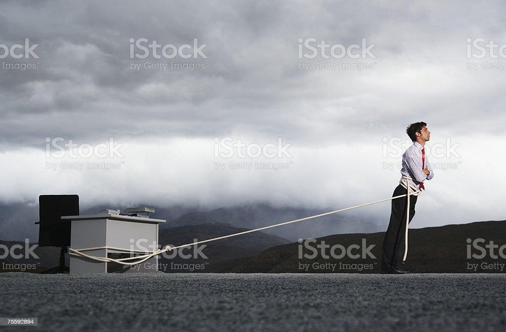 Homem a tentar puxar sua secretária ao ar livre com um foto de stock royalty-free