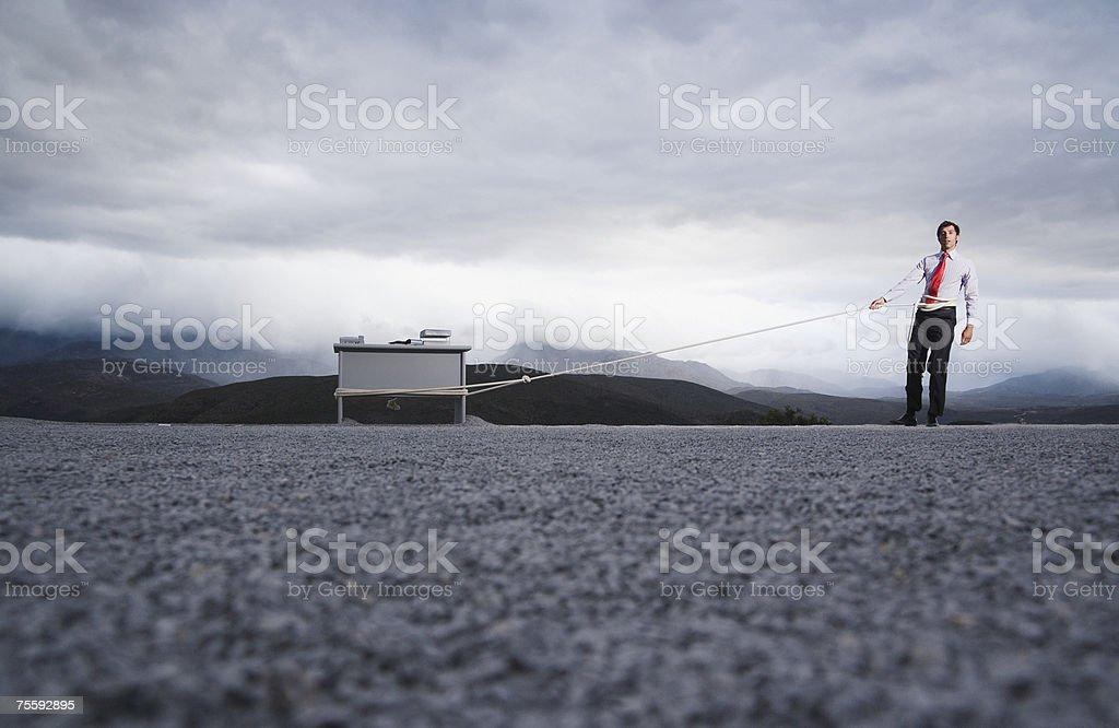 Człowiek próbuje odciągnąć biurku na zewnątrz z długie zbiór zdjęć royalty-free