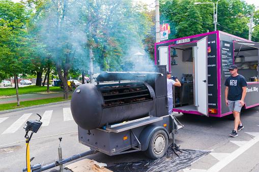 Ploiesti, Romania - July 14, 2018: Man attends barbecue, smoke house oven in shape of train locomotive at The Medieval Festival held in Ploiesti, Prahova, Romania.