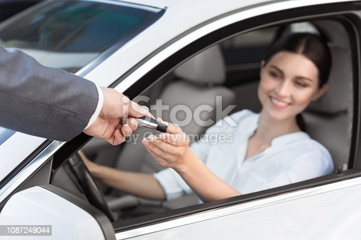 939005154 istock photo Man auto dealer offering car key to woman 1087249044