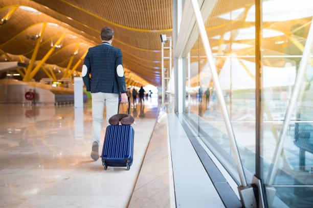 man terug lopen op de luchthaven - airport pickup stockfoto's en -beelden
