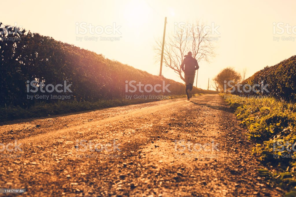 Man backlit in golden sunshine running along a dusty country gravel road. stock photo