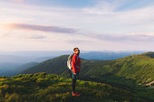 Panoramic photo of a young happy. man enjoying the picturesque summer sunset above the beautiful mountain peaks during his hiking trip in Carpathian mountains