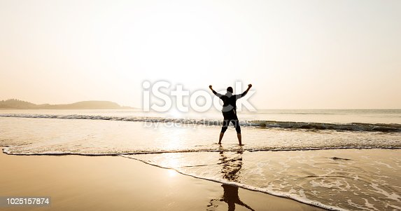 istock Man backpacker standing on beach with arms raised 1025157874