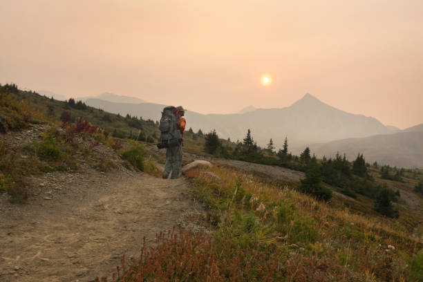 Wildfire smoke fills the morning air in Jasper National Park as the author hikes over the Maccarib Pass.