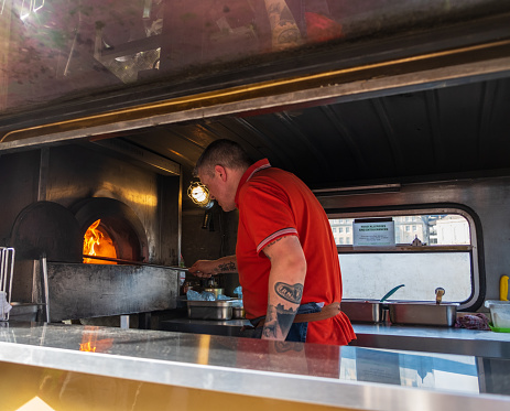 Newcastle, United Kingdom - February 23, 2019: A man bakes pizzas in a rennovated classic van used as a portable canteen serving pizza at Gateshead, Newcastle
