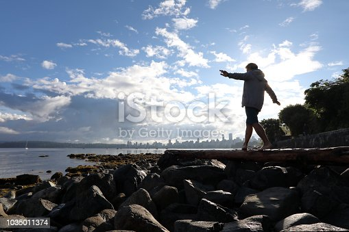 903015102 istock photo Man balances on log by the beach 1035011374