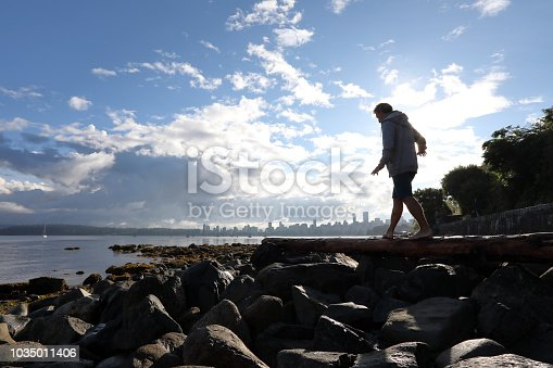 903015102 istock photo Man balances on log by the beach 1035011406