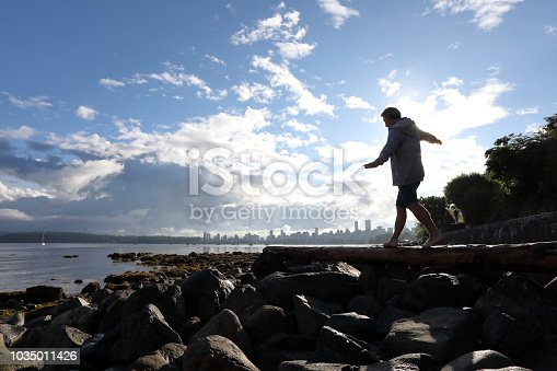 903015102 istock photo Man balances on log by the beach 1035011426