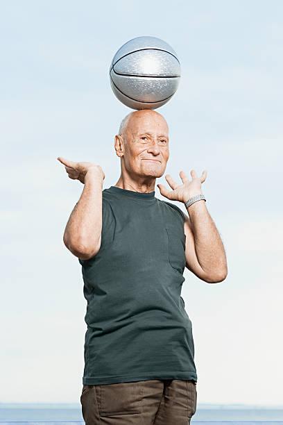 mann balancing basketball auf seinen kopf - senior bilder wasser stock-fotos und bilder