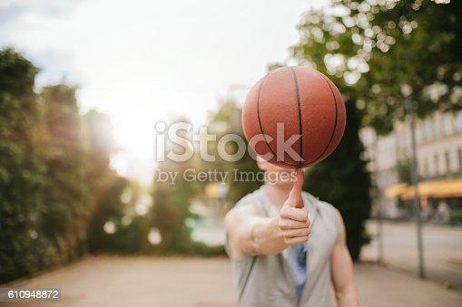 Man balancing basketball on his thumb on outdoor court. Streetball player spinning the ball. Focus on basketball.
