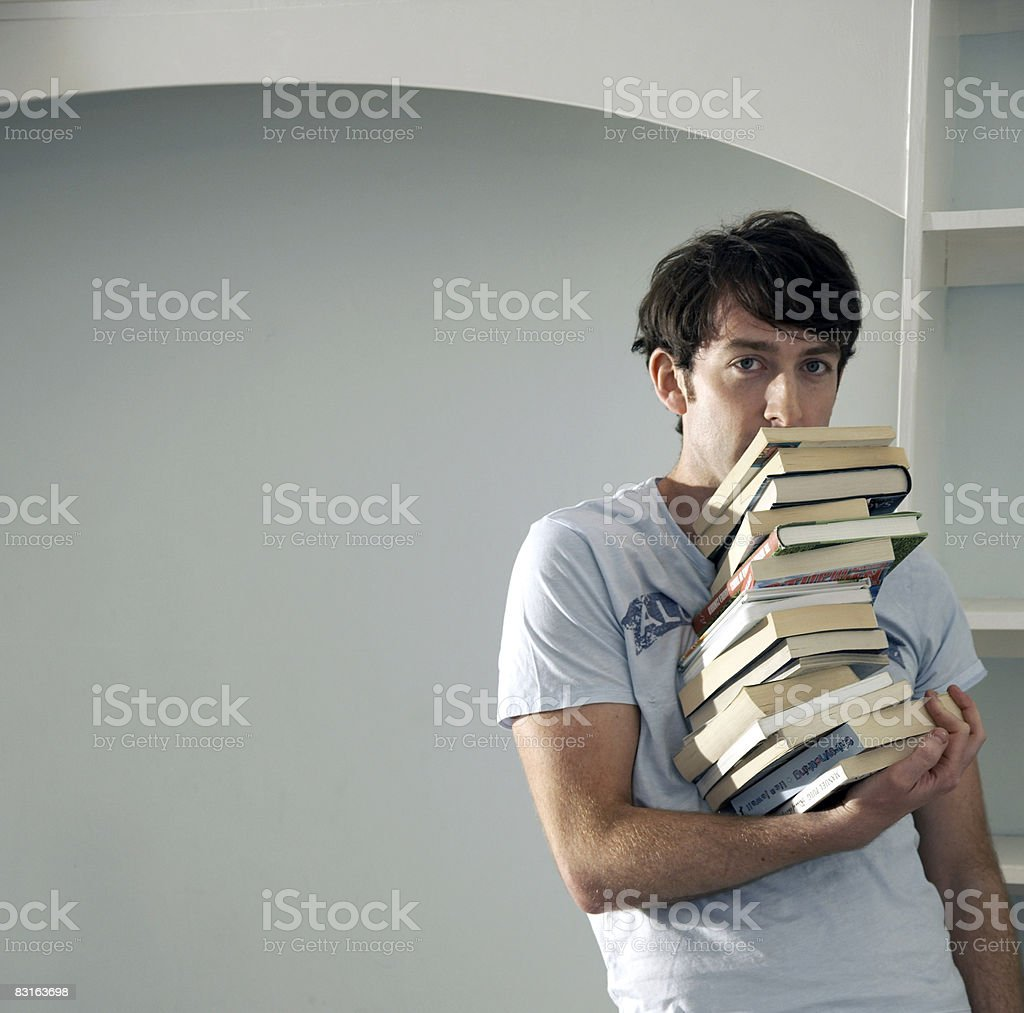 Man balancing big stack of books with one hand royalty-free stock photo