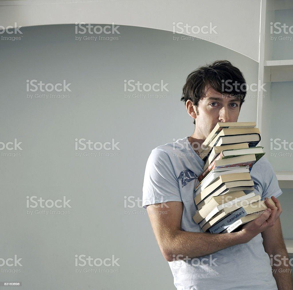 Homme équilibrant grande pile de livres avec une seule main photo libre de droits