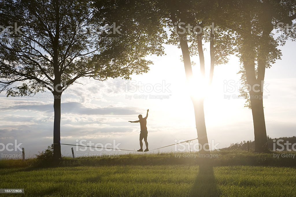 man balancing on a slackline stock photo
