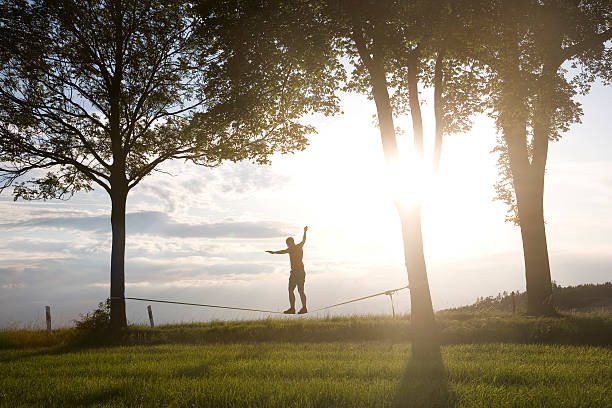 mann balancing auf der slackline - slackline stock-fotos und bilder