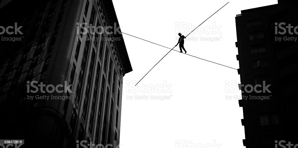 Man balancing on rope high in the sky stock photo