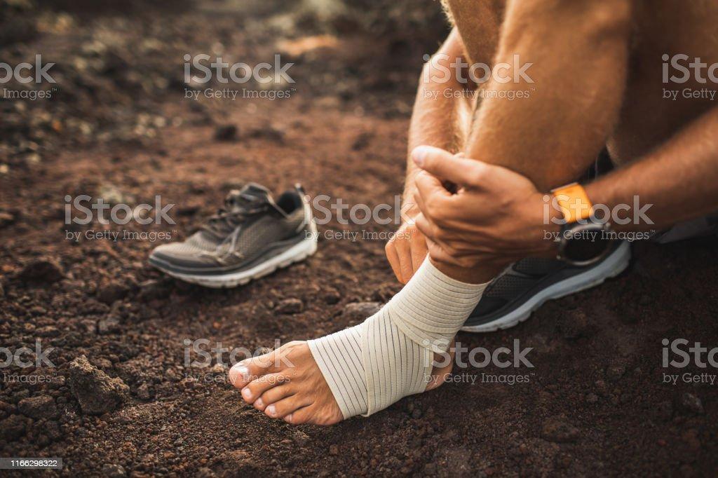Man bandaging injured ankle. Injury leg while running outdoors. First...