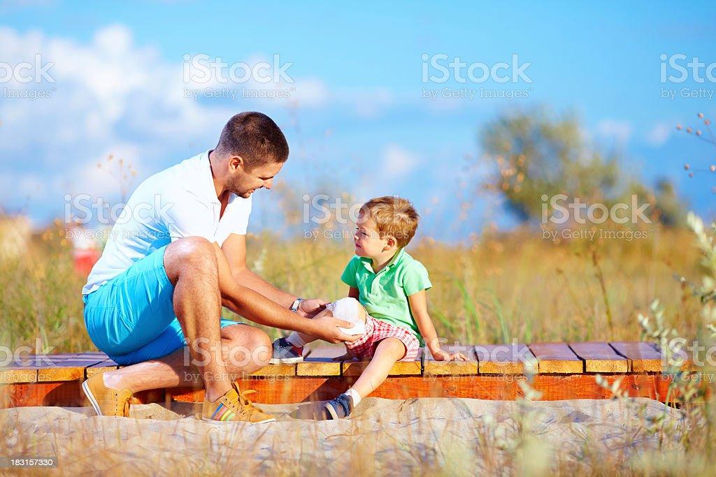 Père bandaging jambe blessée d'enfants - Photo