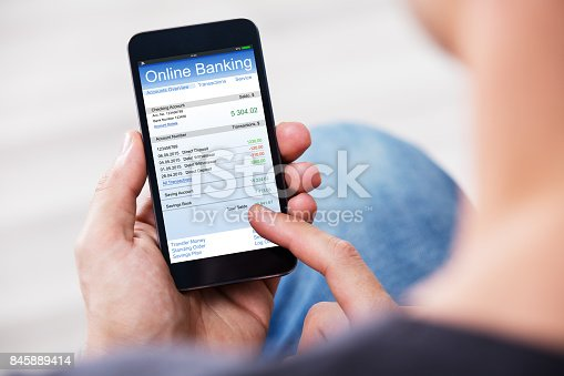 Close-up Of A Man Using Online Banking On Mobile Phone