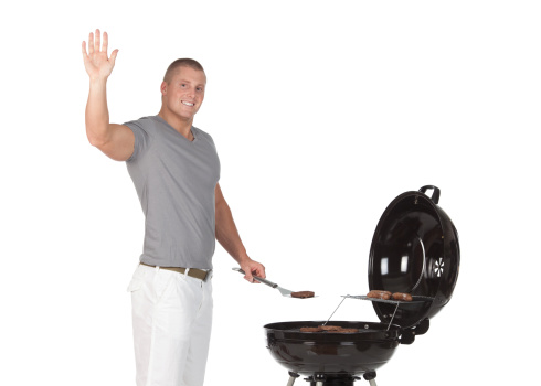 Man barbecuing food and waving his hand