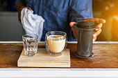 Man barista making Latte coffee with Aeropress system coffee preparation method. Professional coffee brewing cafe. Making coffee at home.