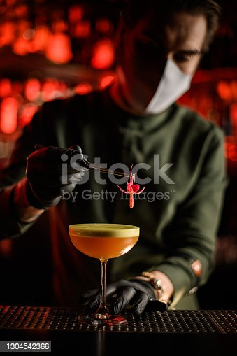 man bartender in gloves and mask holds pink flower with tweezers and decorates glass of cocktail with it