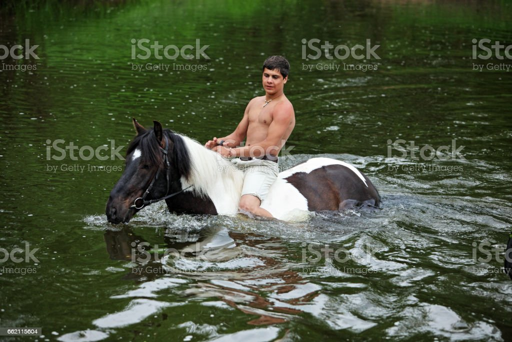 Man bathes in the river horse stock photo