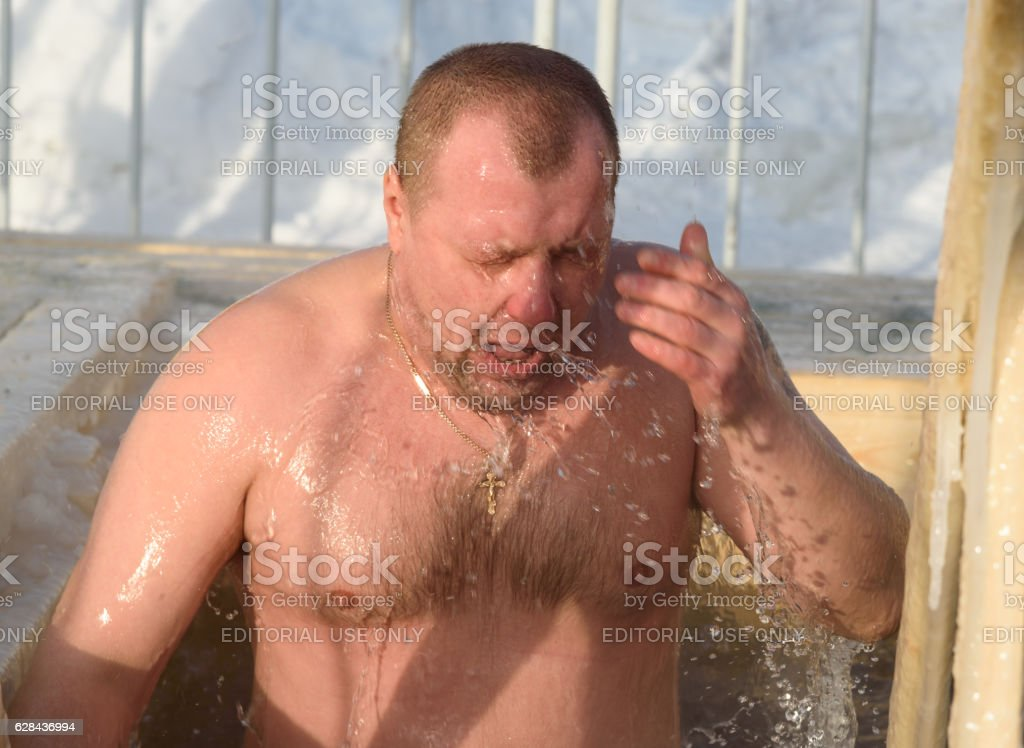 Man bathes into cold water of ice-hole on Epiphany day. stock photo