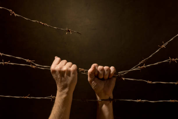 Man Be Handing Fence from Barbed Wire stock photo