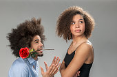 istock man begging woman for forgiveness, holding a rose 486403488