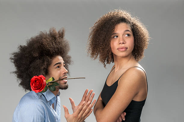 man begging woman for forgiveness, holding a rose Waist up shot of a man with big afro hair and red rose between his teeth begging for forgiveness to young woman looking away  on gray background pleading stock pictures, royalty-free photos & images