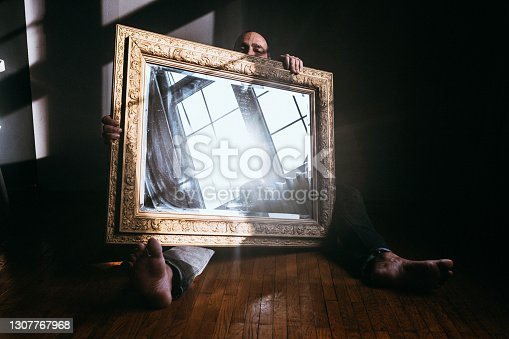 Handsome mature man holding a large mirror with golden vintage frame with window reflection on it