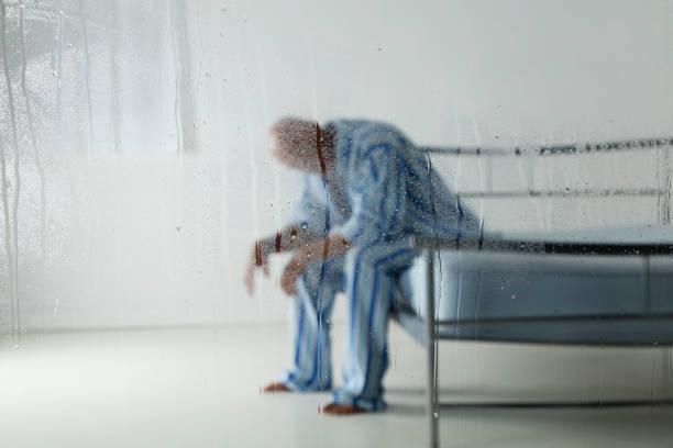 homme derrière une vitre de pluie - hopital psychiatrique photos et images de collection