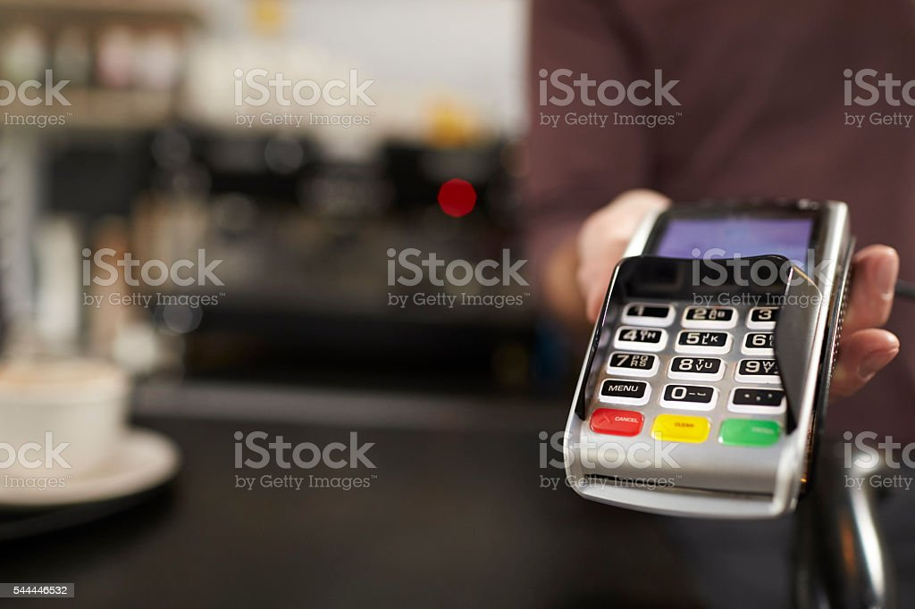Man behind cafe counter offers credit card reader, close up stock photo