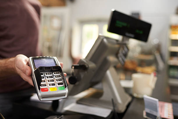 Man behind counter at a cafe offering credit card terminal Man behind counter at a cafe offering credit card terminal cash register stock pictures, royalty-free photos & images