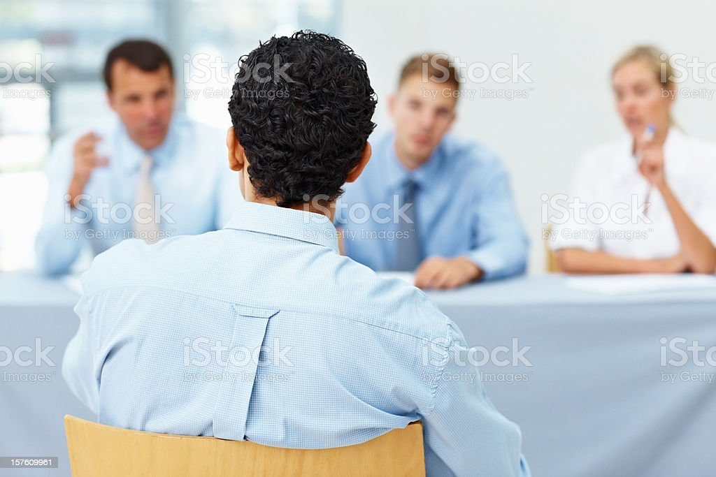 Man being interviewed by a panel of interviewers royalty-free stock photo