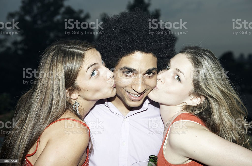 Man being kissed on cheek by two women royalty-free stock photo
