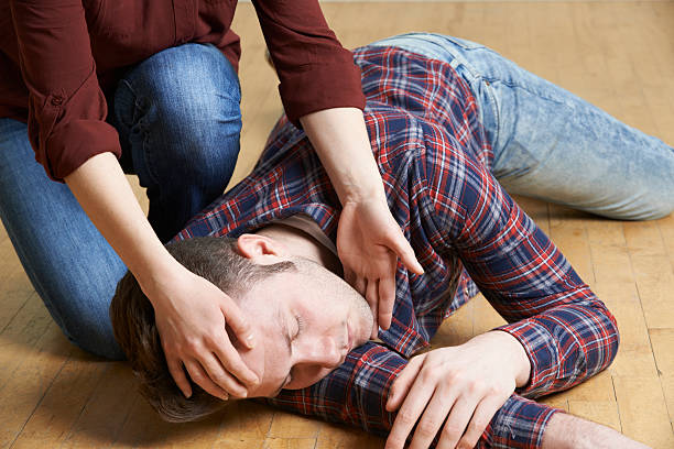 a man being placed in recovery position after accident - position stock pictures, royalty-free photos & images