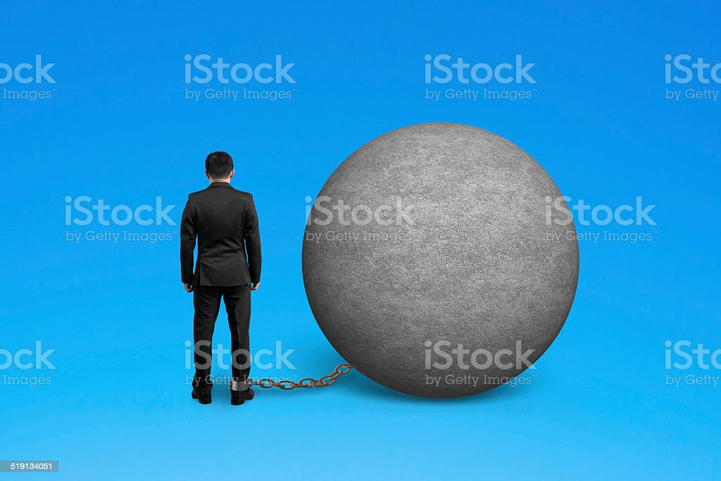 man being trapped with concrete ball stock photo