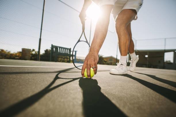 hombre agachado para elegir una pelota de tenis - tenis fotografías e imágenes de stock