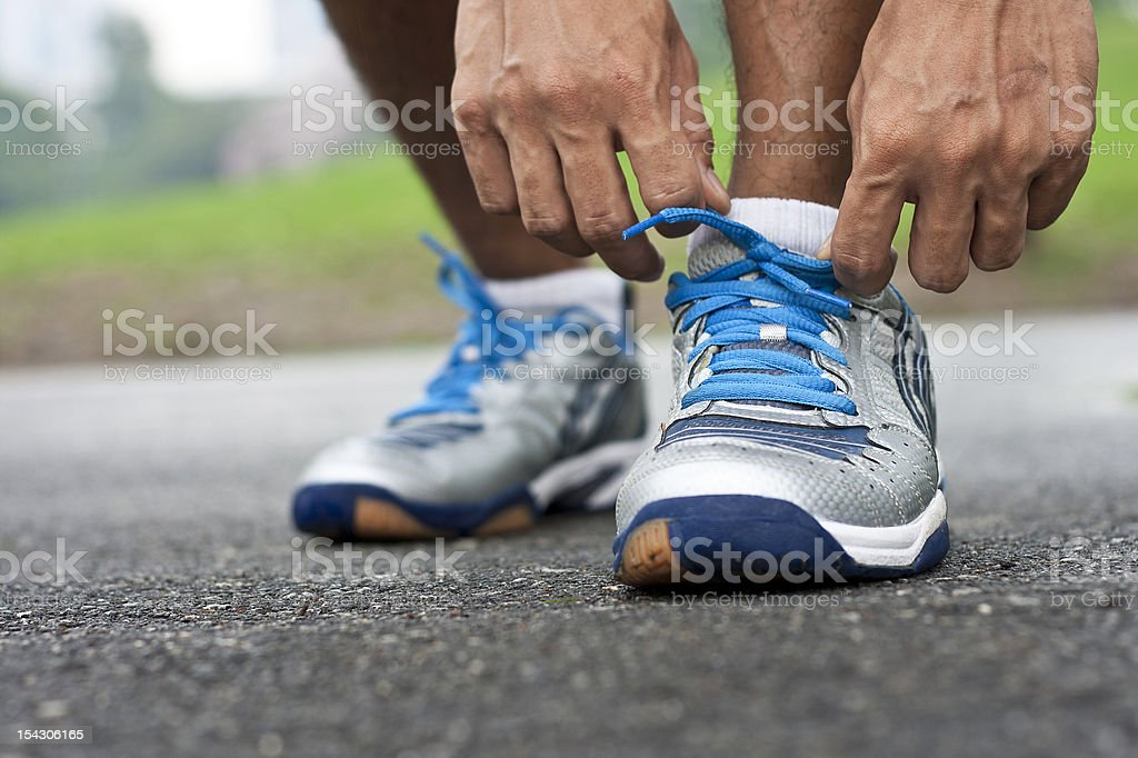Man bending down tying his sports shoes stock photo