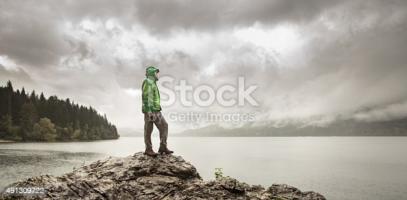 Man standing on a rock beside a dramatic mountain lake after a hike in the rainy, gloomy day. Active lifestyle, outdoor activities, moods and emotions concept.