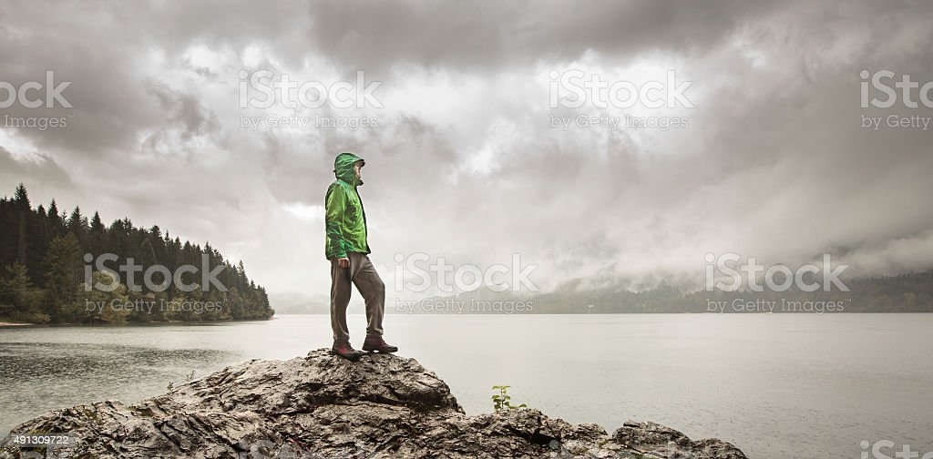 Man beside a mountain lake in rain stock photo