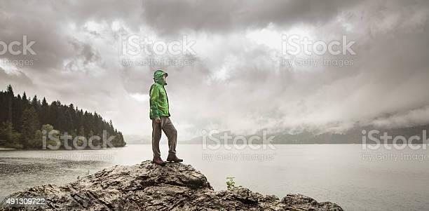 Photo of Man beside a mountain lake in rain